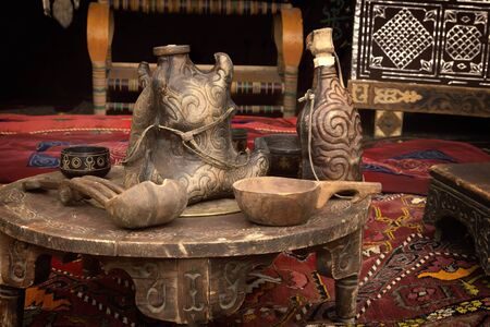 Traditional Kazakh dishes for drinks made of wood and leather are on an old wooden table in a yurt - the home of nomads. Close-up Stock Photo
