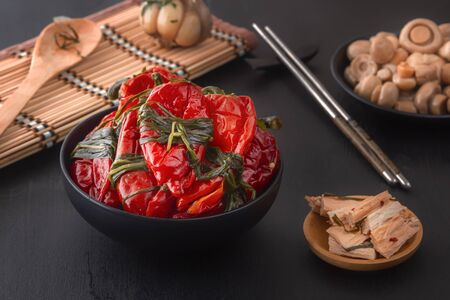 Fermented red hot chili peppers on a black table - traditional Korean food