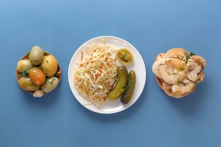 Fermented products pickles, tomatoes, mushrooms, cucumbers and sauerkraut on a blue background .Top view. Copy space
