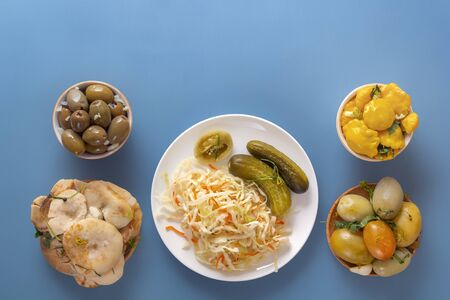 Fermented products cabbage, peppers, pickles, tomatoes, mushrooms, zucchini, garlic on a blue table. Top view. Copy space