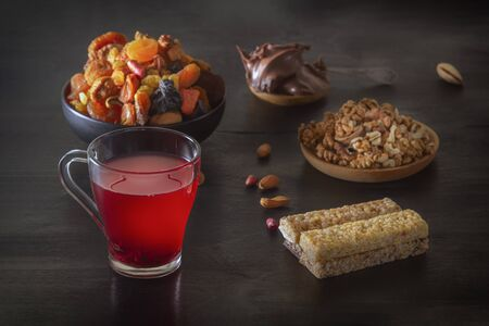Drink from a mix of dried fruits and bars of sports nutrition from nuts, honey, seeds and chocolate paste on a dark table. Low key.