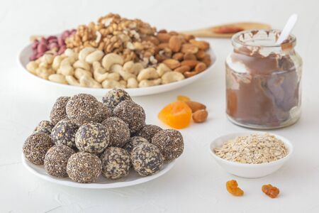 Natural healthy raw energy bites, chocolate paste and mix of dried fruits with nuts on a white table Archivio Fotografico