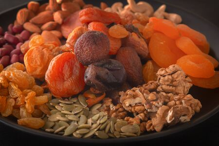 Mix of dried fruits and nuts on a black table. Close-up