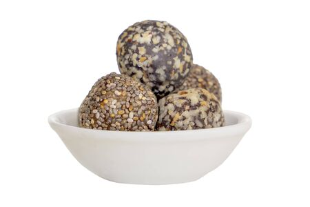 Healthy organic protein energy bites with nuts, cacao, banana, seeds and honey - sports food, vegetarian raw snack. Isolated