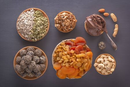 Mix of dried fruits, energy bites, chocolate paste and nuts on a dark table. Top view Standard-Bild