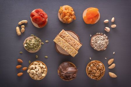 Bars of sports nutrition from nuts, seeds and chocolate paste - vegetable natural protein, a mixture of dried fruits, assorted nuts and seeds on a dark table. Top view