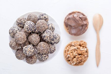Natural healthy raw energy bites, chocolate paste and mix of dried fruits with nuts on a white table. Top view Archivio Fotografico