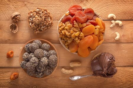 Natural healthy raw energy bites, chocolate paste and mix of dried fruits with nuts on a wooden table. Top view