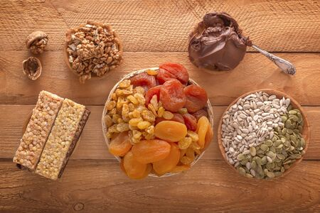 Mix of dried fruits, energy bites, chocolate paste, assorted nuts and seeds on a wooden table.Top view Standard-Bild