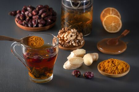 Medicinal herbal tea in a glass cup, ginger, walnut, turmeric, honey, lemon and dry rosehip berries - a means to increase immunity from the virus