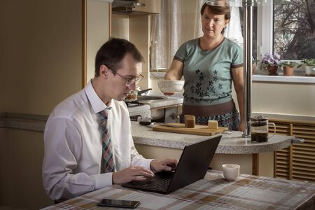 Young man works at a computer at home on the background of a woman busy cooking. Toned