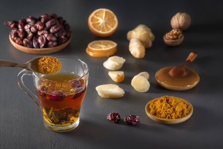 Medicinal herbal tea in a glass cup, ginger, walnut, turmeric, honey, lemon and dry rosehip berries - a means to increase immunity from the virus Standard-Bild