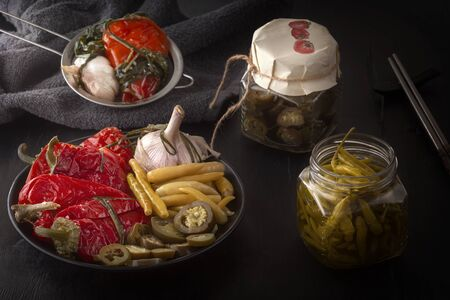 Fermented red and green hot peppers and garlic on a dark wooden table. Low key.