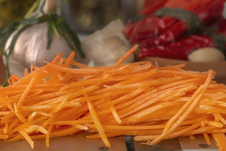 Carrots grated on a hand grater on the background of differentiated products - pepper, garlic, carrots. Close-up