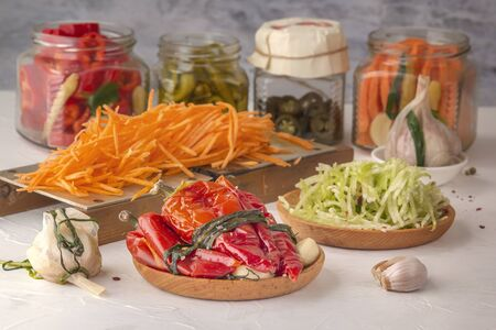 Fermented red hot peppers to enhance immunity with spices and grated carrots on a hand grater on a light wooden table against a background of glass jars with pickled products 스톡 콘텐츠