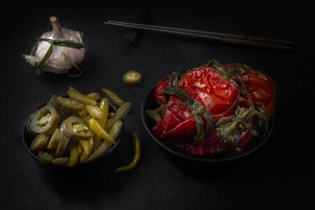 Fermented hot pepper and garlic on a dark wooden table. Low key.
