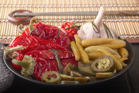 Fermented red and green hot peppers and garlic on a background of a straw mat with chopsticks. Close-up