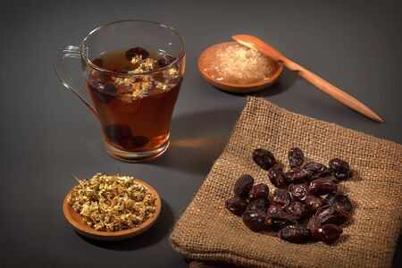 Herbal tea with medical chamomile and dried rosehips on a dark table Banque d'images