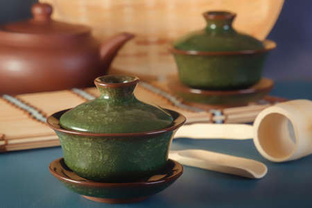 Traditional asian porcelain cups and tea ceremony items on blue table 스톡 콘텐츠