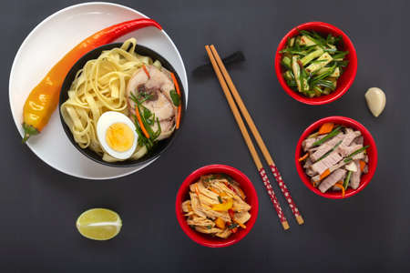 Noodles with pieces of meat and egg in a black plate and dim sums with different traditional snacks of mushrooms, soy and vegetables with chopsticks on a dark table. View from above. Asian food concept