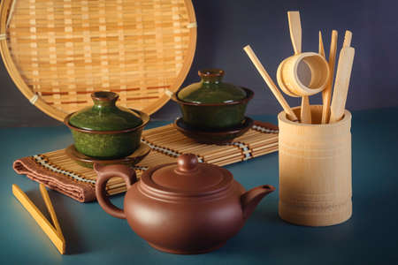 Chinese clay teapot, traditional porcelain cups and tea ceremony items on blue table
