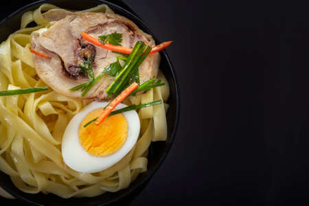 Noodles with pieces of meat and an egg in a black plate on a dark table. View from above. Asian food concept. Copy space. Close-up
