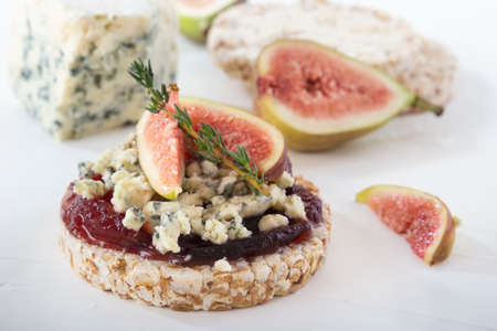 Puffed exploded wheat grains with slices of figs and blue cheese on a thin layer of jam on a light wooden table against a background of fruits and a cheese head. Close-up
