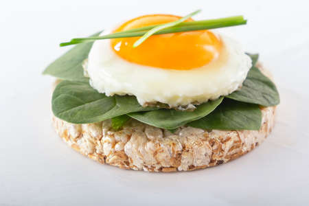 Puffed exploded wheat grains with fried egg and spinach leaves on a light wooden background. Close-up