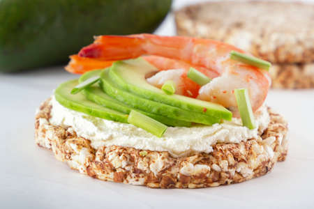 Puffed exploded wheat grains with shrimps and avocado slices on a thin layer of soft cheese on a light wooden table. Close-up 스톡 콘텐츠