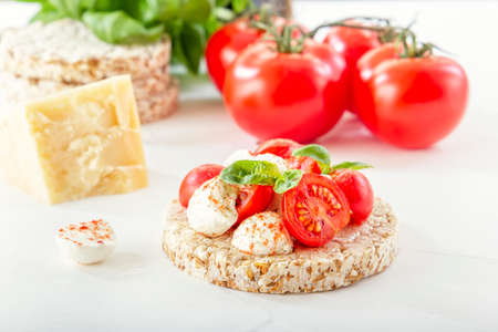 Puffed exploded wheat grains with slices of mozzarella and chili tomato sprinkled with pepper on a light wooden table against the background of a head of cheese. tomatoes and herbs. Close-up