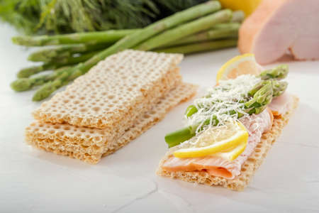 Crispy low calorie wheat crackers with turkey meat, asparagus and lemon slices on a white wooden table. Close-up