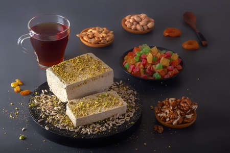 Sunflower halva sprinkled with crushed nuts on a black plate along with pistachios, peanuts, dried apricots, candied syrup and a glass of tea on a dark background. Eastern sweets