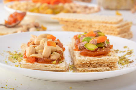 Crispy low-calorie wheat crackers with peanuts, pistachios, raisins and candied fruits on a thin layer of apricot jam on a white plate with oriental sweets in the background. Close-up