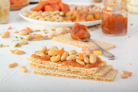Crispy low-calorie wheat crackers with peanuts and dried apricots on a thin layer of apricot jam on a white table against a background of oriental sweets. Close-up