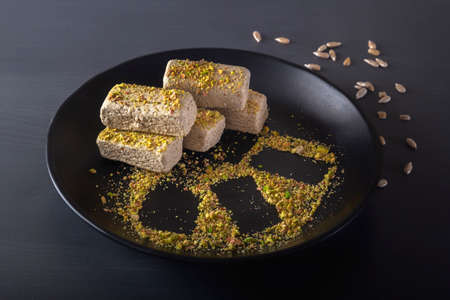 Sunflower halva sprinkled with crushed nuts and pistachios on a black plate on a dark background. Close-up