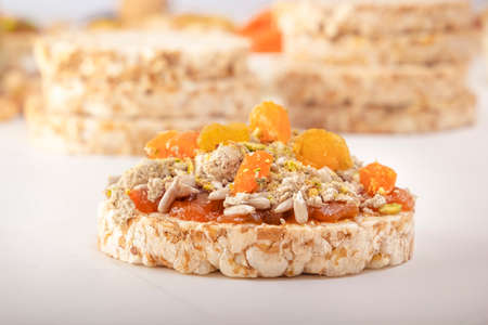 Puffed exploded wheat grains with peeled sunflower seeds, halva and raisins on a thin layer of apricot jam on a white wooden table