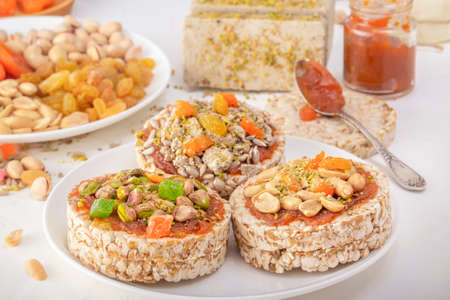 Puffed exploded wheat grains with peanuts and dried apricots, pistachios and sunflower seeds, halva and raisins on a layer of apricot jam on a white plate against a background of oriental sweets. 스톡 콘텐츠