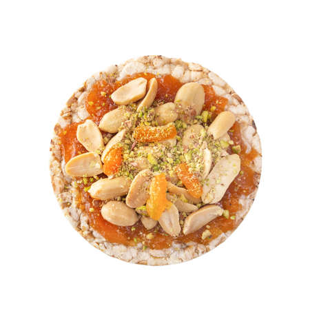 Puffed exploded wheat grains with peanuts and dried apricots on a thin layer of apricot jam on a white wooden table. Isolated. Top view