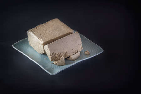 Sunflower halva on a blue plate on a dark background. Eastern sweets. Place for text