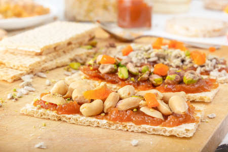 Crispy low-calorie wheat crackers with peanuts, pistachios, raisins and candied fruits on a thin layer of apricot jam on a wooden board against a background of oriental sweets. Close-up 스톡 콘텐츠