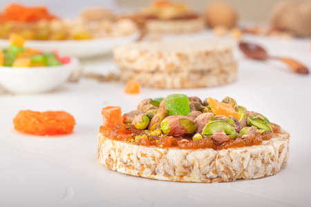 Puffed exploded wheat grains with pistachios and candied fruits on a thin layer of apricot jam on a background of oriental sweets on a white wooden table. Close-up