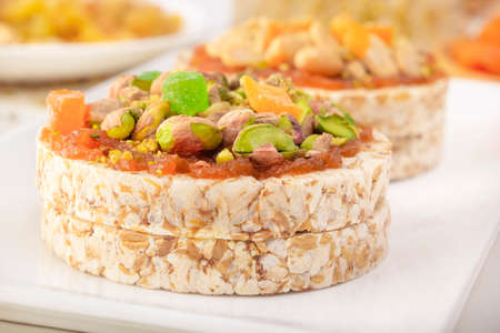 Puffed exploded wheat grains with pistachios and candied fruits on a thin layer of apricot jam and Puffed exploded wheat grains with peanuts and dried apricots on a white plate. Close-up 스톡 콘텐츠
