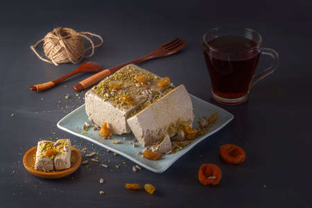 Sunflower halva sprinkled with crushed nuts on a blue plate with pistachios, dried apricots and a glass with tea on a dark background. Eastern sweets