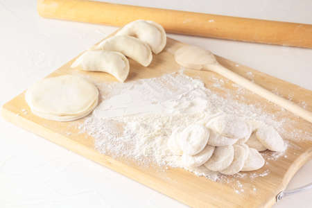 Blanks for rolling dough in flour and raw manti, dumplings, or wontons of dough stuffed with minced meat on a kitchen board with a rolling pin on a white background. Homemade food.