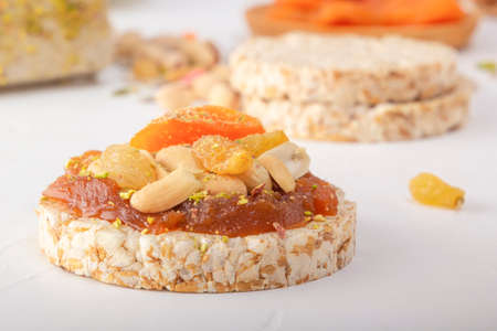 Puffed exploded wheat grains with peanuts and dried apricots on a thin layer of apricot jam on a background of oriental sweets on a white wooden table. Close-up