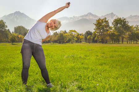 Elderly woman is engaged in fitness with a dumbbell in isolation mode outdoors in a park against a background of mountains on a sunny day 스톡 콘텐츠