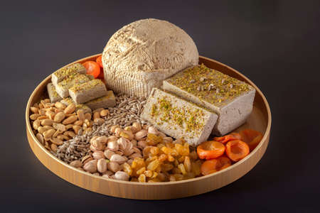 Sunflower halva sprinkled with crushed nuts and raisins on a wooden dish with pistachios, peanuts, dried apricots, candied fruit syrup and on a dark background. Eastern sweets. Copy space