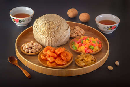 Sunflower halva sprinkled on a wooden platter with pistachios, peanuts, dried apricots, candied fruit syrup and Asian tea cups on a dark background. Eastern sweets. 스톡 콘텐츠