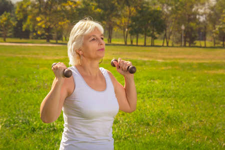 Elderly woman lifts dumbbells while doing fitness in a city park against the backdrop of mountains on a sunny day. Close-up 스톡 콘텐츠