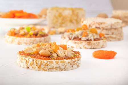 Puffed exploded wheat grains with peanuts and dried apricots on a thin layer of apricot jam on a background of oriental sweets on a white wooden table